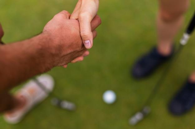 Jogadores de golfe de close-up, apertando as mãos
