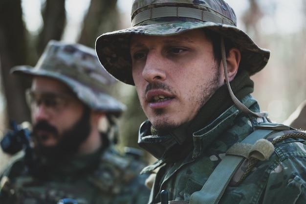 Jogadores de jogos militares de airsoft em uniforme de camuflagem e rifle de assalto armado.