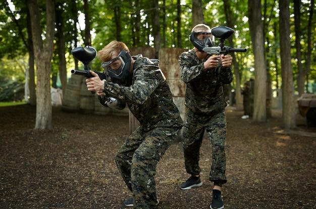 Jogadores de paintball de uniforme e máscaras brincando no playground da floresta. esporte radical com arma pneumática e balas ou marcadores de tinta, jogo de equipe militar ao ar livre, táticas de combate
