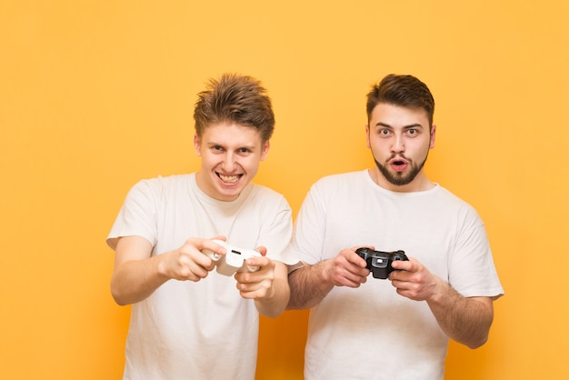 Jogadores emocionais com gamepad na mão, jogando videogame focado no amarelo