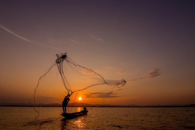 Jogando a rede de pesca durante o pôr do sol