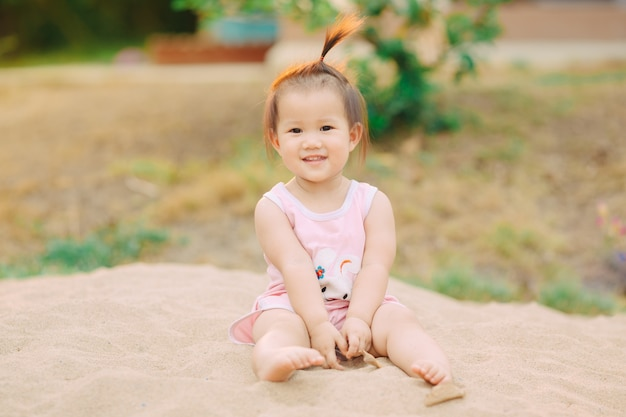 Jogando areia no recreio para o bebê e a criança é uma atividade importante para a criança develo