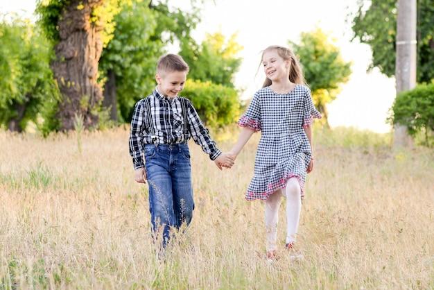 Jogando as crianças no campo verde durante o dia quente de verão