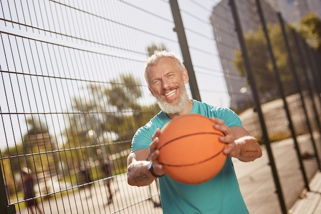Jogando basquete, alegre homem de meia idade em roupas esportivas, segurando uma bola de basquete e sorrindo para