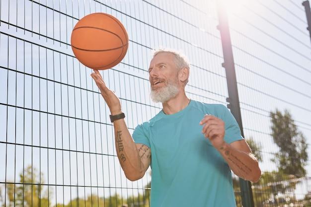 Jogando basquete ao ar livre, um homem idoso feliz em roupas esportivas girando uma bola de basquete em seu