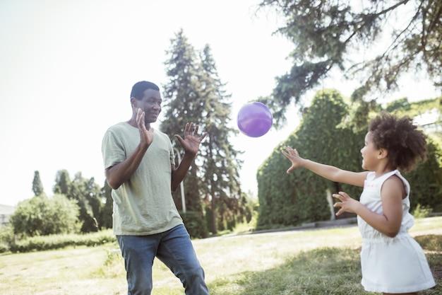 Jogando bola. pai e uma linda garota jogando bola no parque