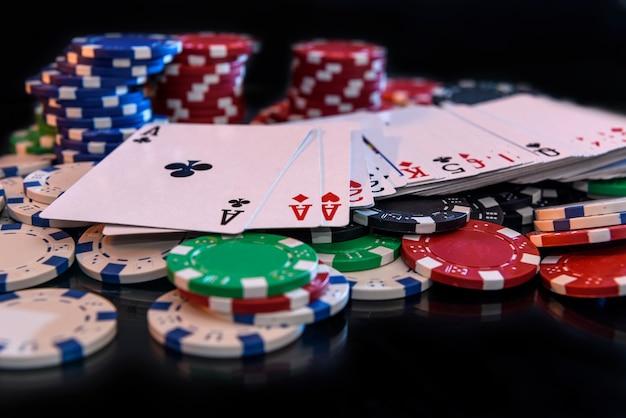 Jogando cartas com fichas de pôquer na superfície preta