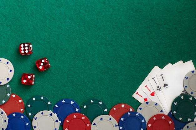 Jogando cartas, dadinhos e fichas de poker de cima na mesa de poker verde