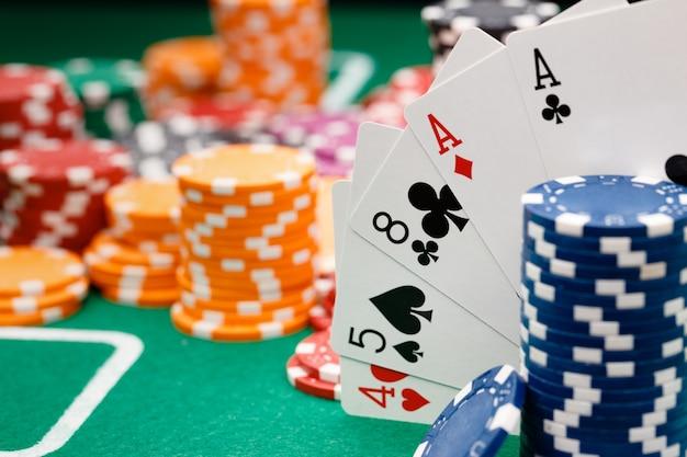 Jogando cartas e fichas na superfície verde da mesa do cassino