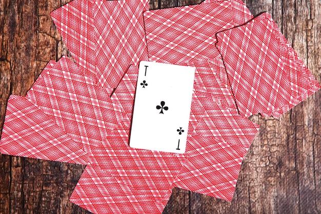 Jogando cartas espalhadas na mesa. plano de fundo de cartas de baralho espalhadas enchendo o verso invertido com ace cruzado para cobrir todo em madeira texturizada. vista superior, close-up. espaço de direitos autorais para o site