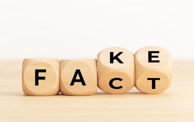 Jogando dados de madeira com palavras falsas e factuais