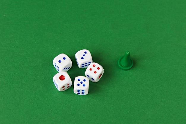 Jogando dados e ficha verde na superfície verde