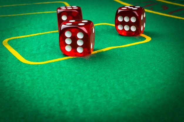 Jogando dados em uma mesa de jogo verde. jogando um jogo de dados. rolos de dados vermelhos do casino. conceito de lançamento de dados