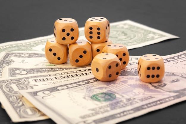 Jogando dices e pilha de notas de dólares americanos.