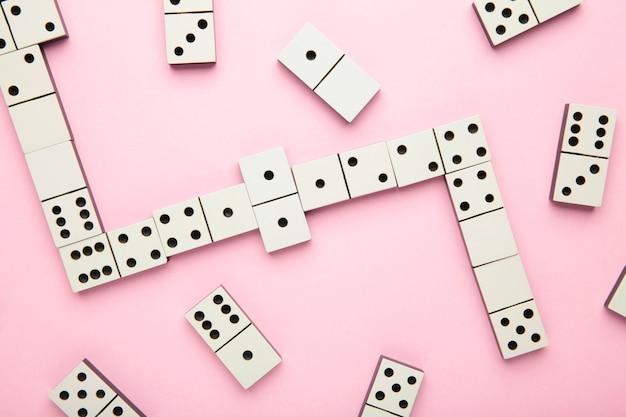 Jogando dominó na superfície rosa