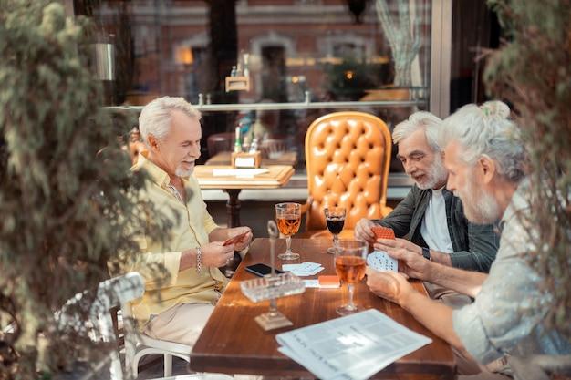Jogando e bebendo. três homens aposentados jogando e bebendo álcool no fim de semana