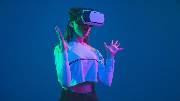 Jogando em ação. retrato de mulher jovem caucasiana isolado no fundo azul do estúdio em luz de néon. linda modelo feminino. conceito de emoções humanas, expressão facial, vendas, anúncio, cultura jovem.