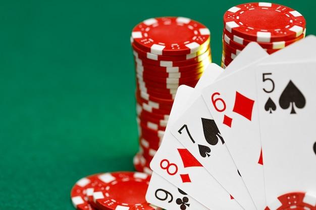 Jogando fichas e cartas vermelhas na mesa de pôquer