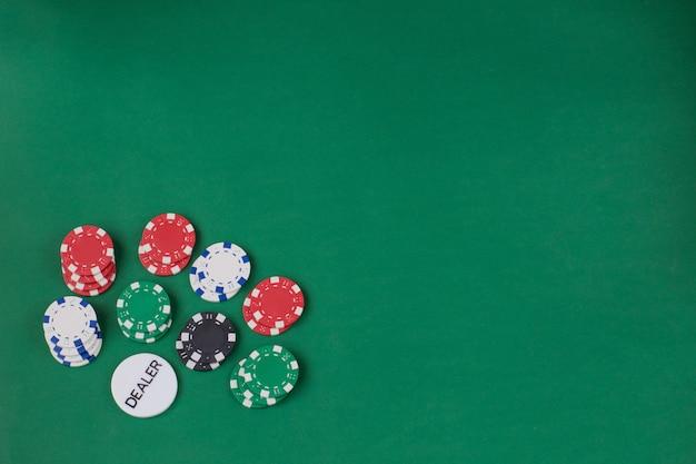 Jogando fichas em um fundo verde e um chip de revendedor