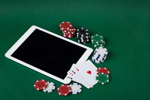 Jogando fichas, quatro ases e um tablet em uma mesa verde