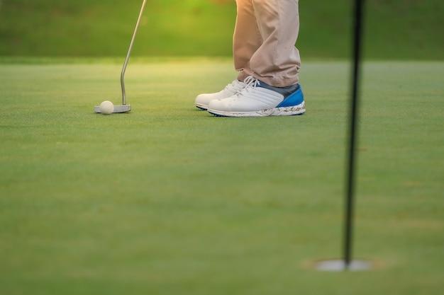 Jogando golfe, preparando-se para atirar em homem colocando no verde