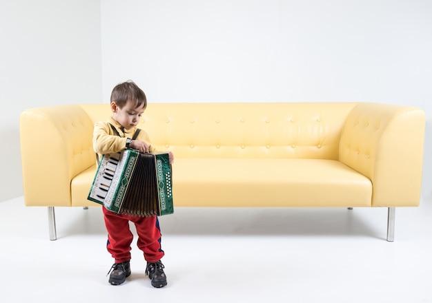 Jogando harmônica por um menino pequeno