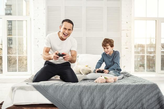 Jogando jogos. pai bonito, exuberante e musculoso sorrindo e brincando com o filho e eles segurando controles remotos