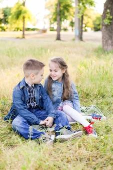 Jogando miúdos no campo verde durante o verão. assento de menino e menina na grama