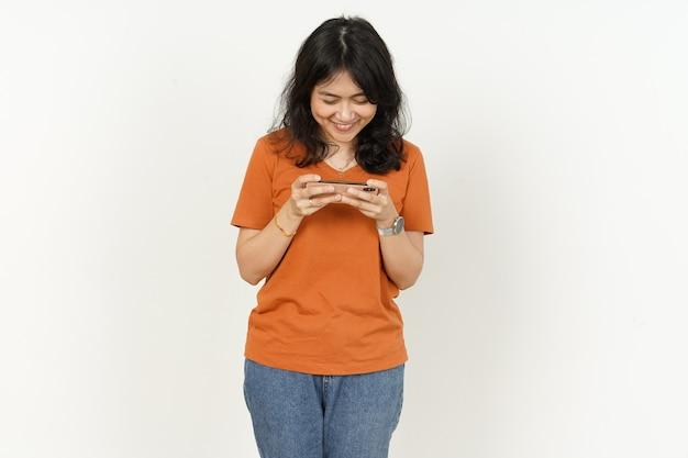 Jogando no smartphone e ganhando uma linda mulher asiática usando camiseta laranja isolada no branco