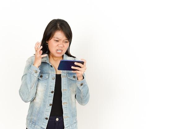 Jogando no telefone com a cara zangada de uma bela mulher asiática vestindo jaqueta jeans e camisa preta