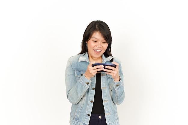 Jogando no telefone com o rosto feliz de uma linda mulher asiática vestindo jaqueta jeans e camisa preta