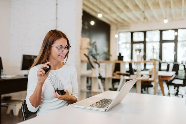 Jogando no trabalho. jovem mulher que relaxa com furtivo na mesa de escritório no estúdio criativo.
