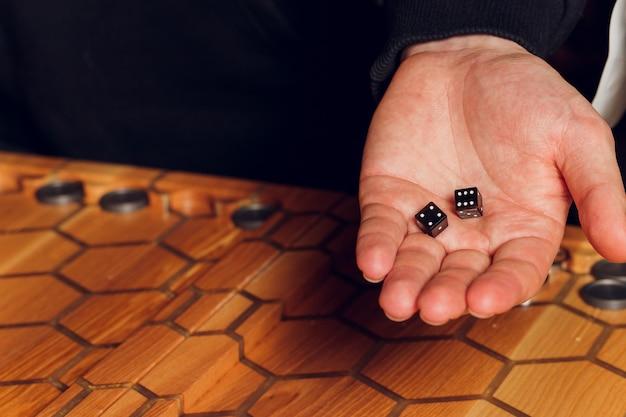 Jogando o jogo de gamão. homem joga o jogo de tabuleiro. dados na placa de madeira.