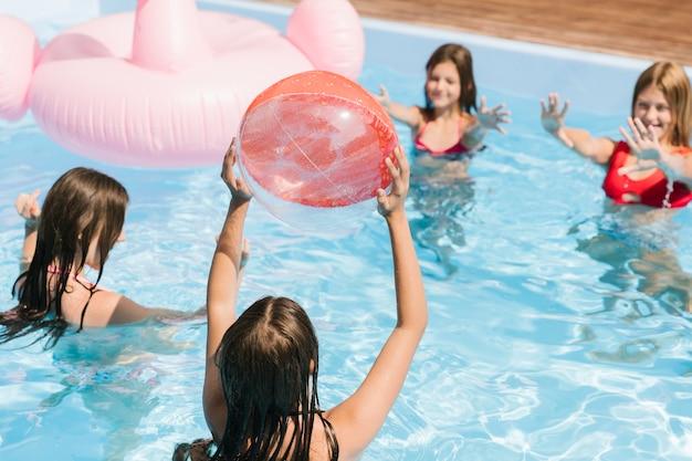 Jogando o tempo na piscina com uma bola de praia