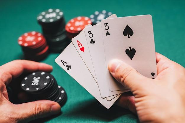 Jogando poker no cassino. cartas com dois pares na mão do jogador fazendo uma aposta com fichas