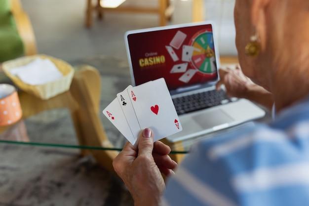 Jogando pôquer cassino on-line mulher sênior estudando em casa fazendo cursos on-line