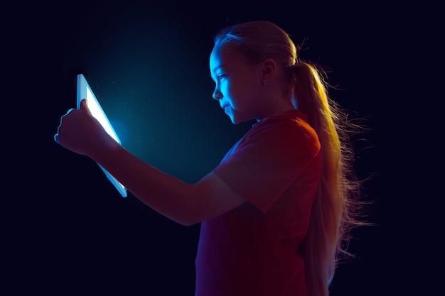 Jogando. retrato da menina caucasiana isolado no fundo escuro do estúdio em luz de néon. bela modelo feminino usando tablet. conceito de emoções humanas, expressão facial, vendas, anúncio, tecnologia moderna, gadgets.