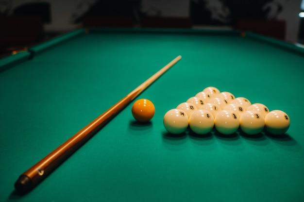 Jogando sinuca em uma mesa verde. as bolas e o taco estão dispostos sobre a mesa.