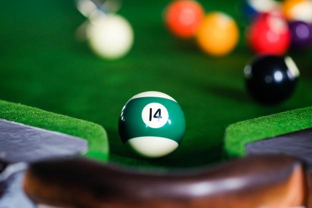 Jogando sinuca ou preparando-se com o objetivo de atirar bolas de bilhar em uma mesa de bilhar verde.