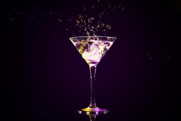 Jogando um cubo de gelo em um copo com um coquetel saboroso no escuro