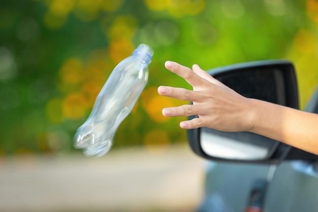 Jogando uma garrafa de plástico pela janela do carro