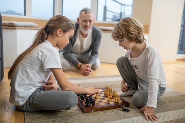 Jogando xadrez. irmãos jogando xadrez enquanto o pai assistia