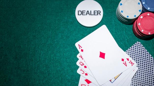 Jogar cartas e fichas de casino em fundo verde