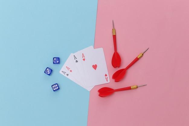 Jogatina. quatro ases, dados e dardos em fundo azul rosa.