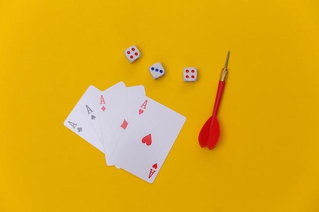 Jogatina. quatro ases, dados e dardos em um fundo amarelo. vista do topo