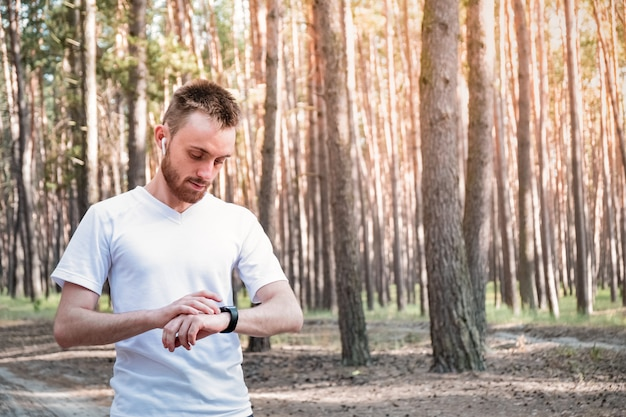 Jogeer masculino, verificando o relógio inteligente ao ar livre