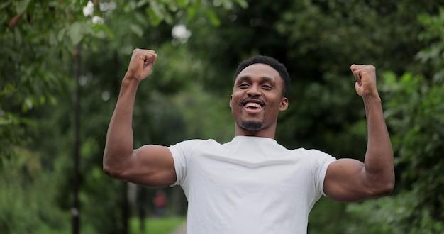 Jogger levantando as mãos no parque, tiro em câmera lenta. jovem americano africano primeiro terminar a competição de corrida de triatlo, levantando a mão.
