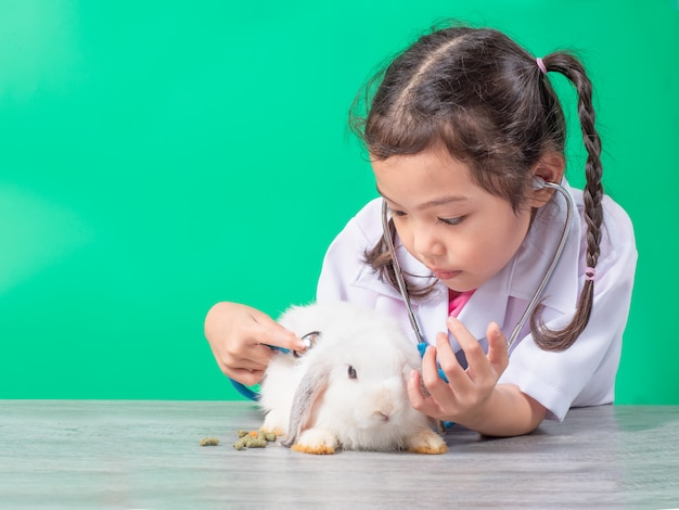 Jogo bonito menina asiática, examinando um coelho branco de bebê sobre verde