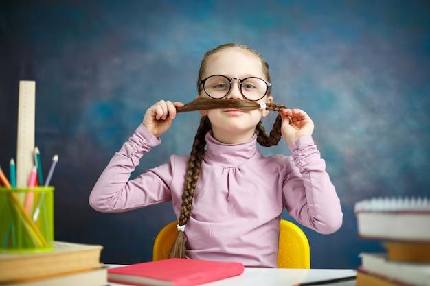 Jogo da menina da escola primária com retrato longo da trança