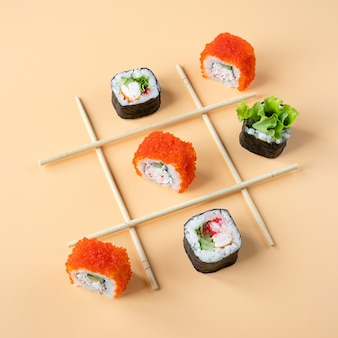 Jogo da velha com sushi em fundo laranja